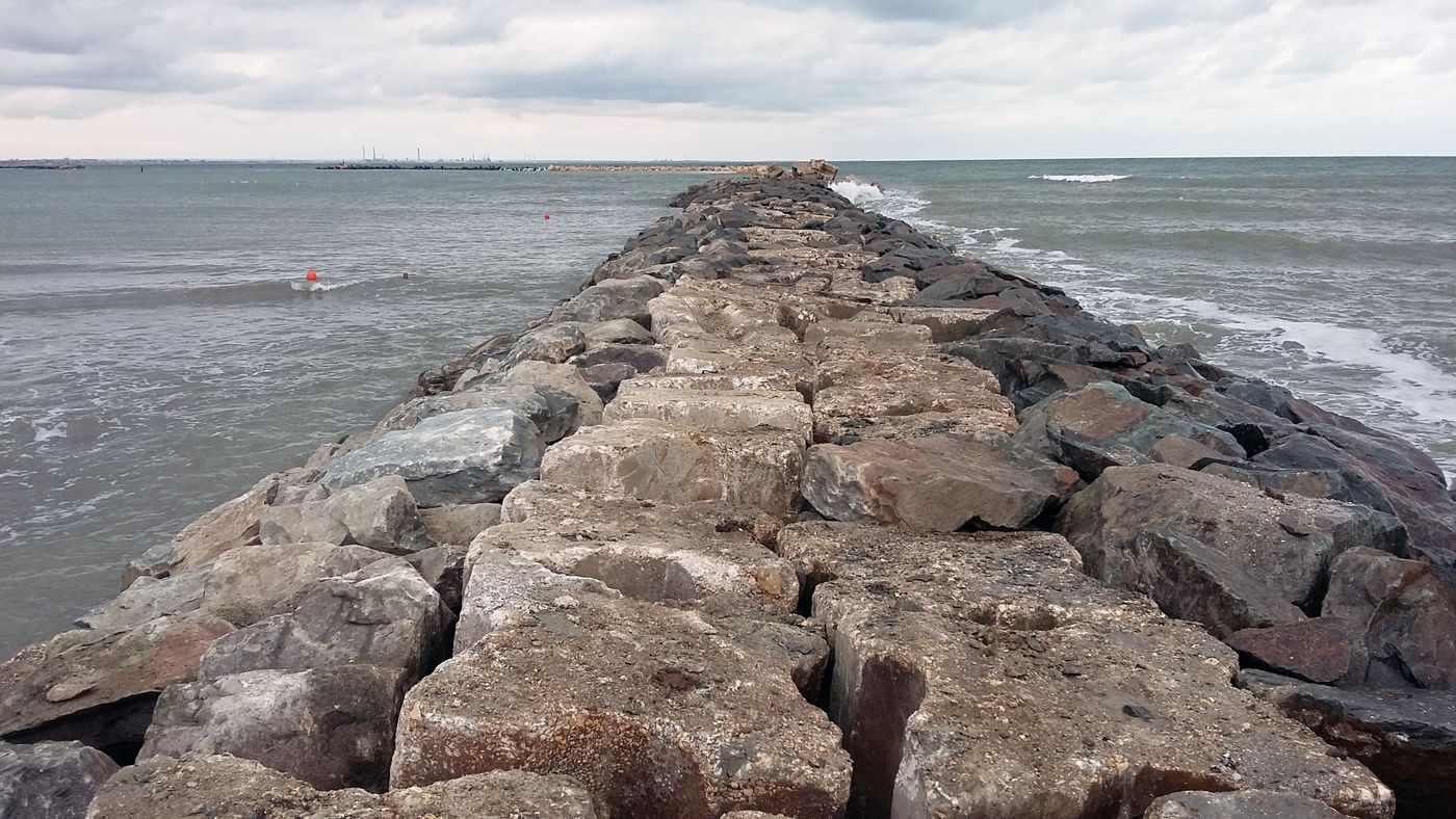 Photo: massive breakwater reaching out straight into the sea, gentle waves on both sides