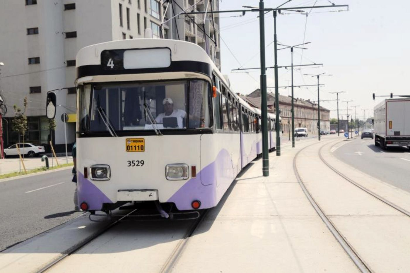 Photo: white and violet tramway driving on the new tracks; on the right, electricity poles and tracks; on the far right, a truck and cars on the street; an apartment building in the background opposite