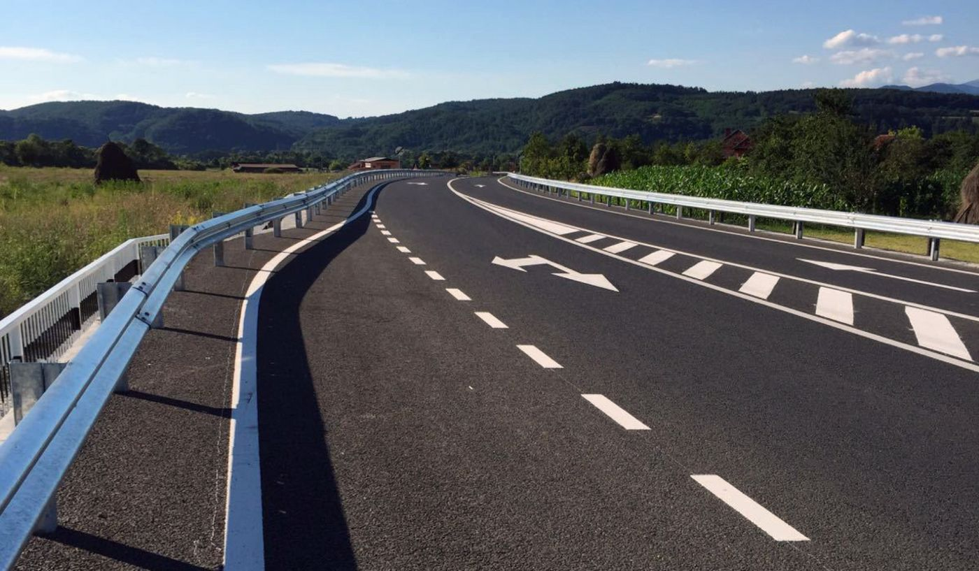 Photo: freshly asphalted and marked road, with a new pavement and guardrails, embedded in a rural landscape
