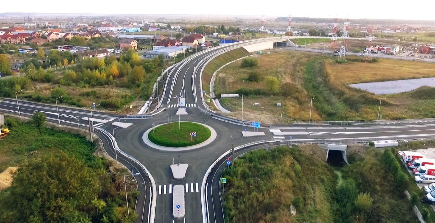 Photo: aerial view of four roads ending in a roundabout; the overpass in the background; surroundings of green grass, trees, some houses and parked cars