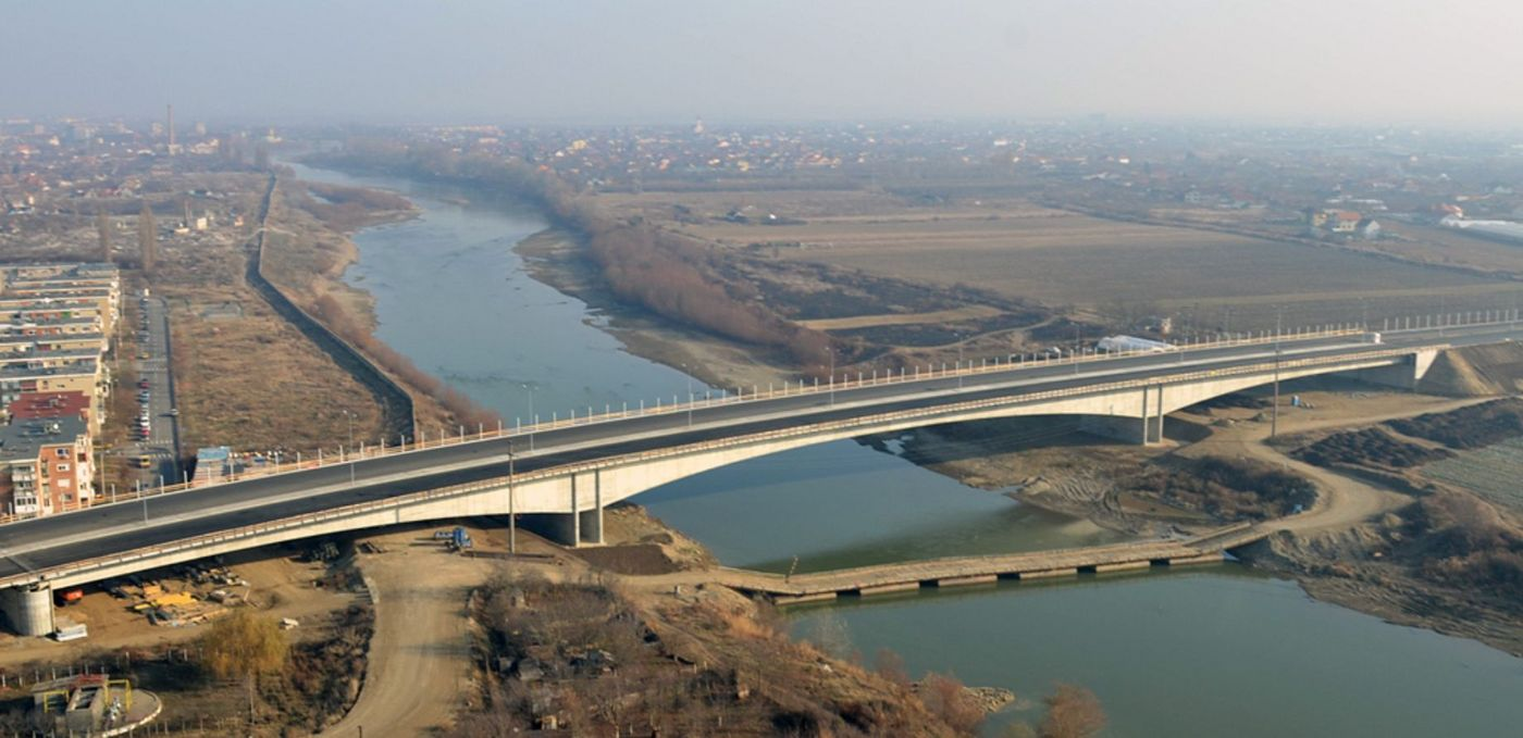 Photo: aerial view of the bridge traversing the Mureș River in misty sunlight; rural area on the right; suburban houses on the left; the city of Arad in the background