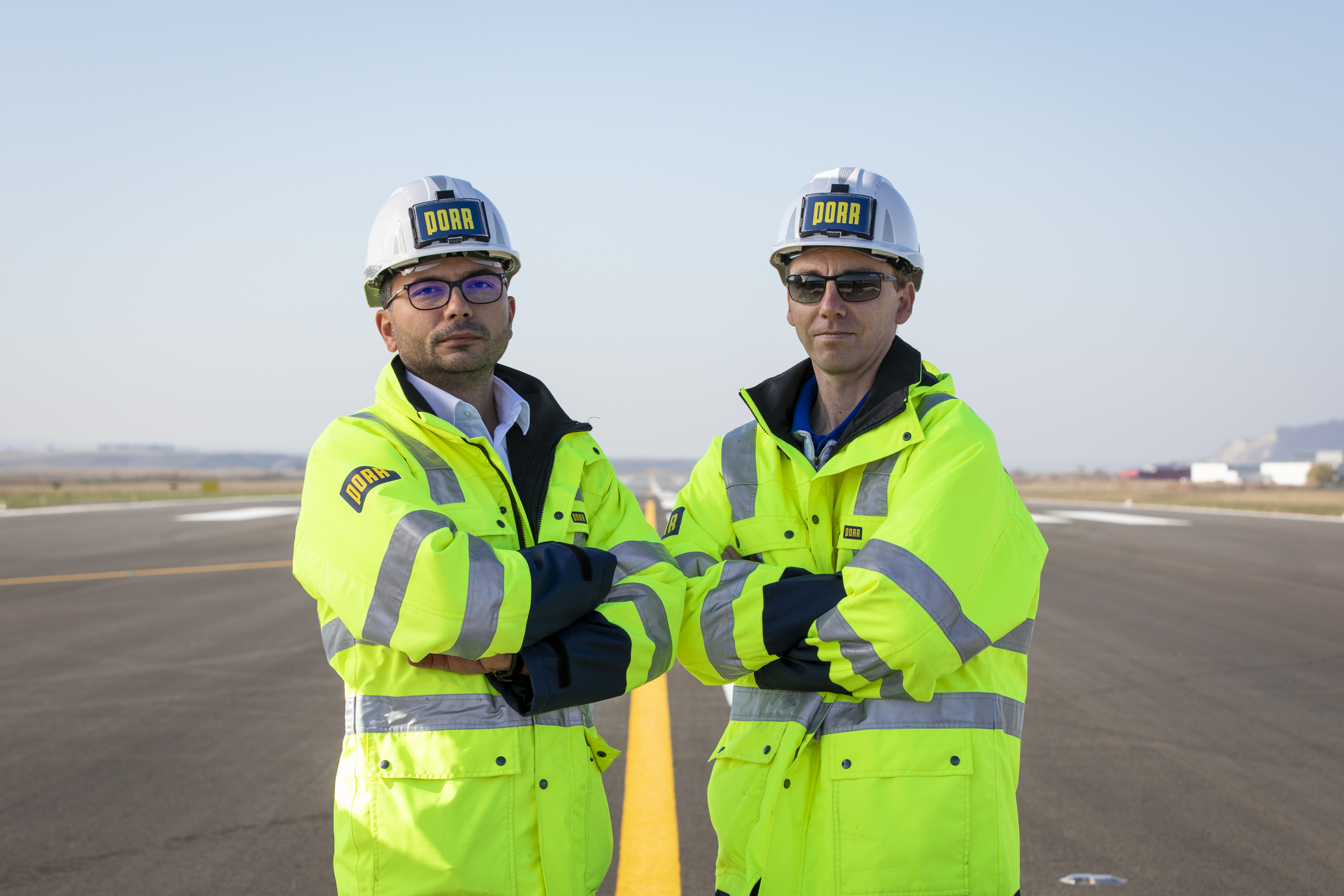 Photo: two men with work jackets and PORR helmets, one with glasses, the other with sunglasses, standing on an airport runway, looking towards the camera with arms confidently crossed
