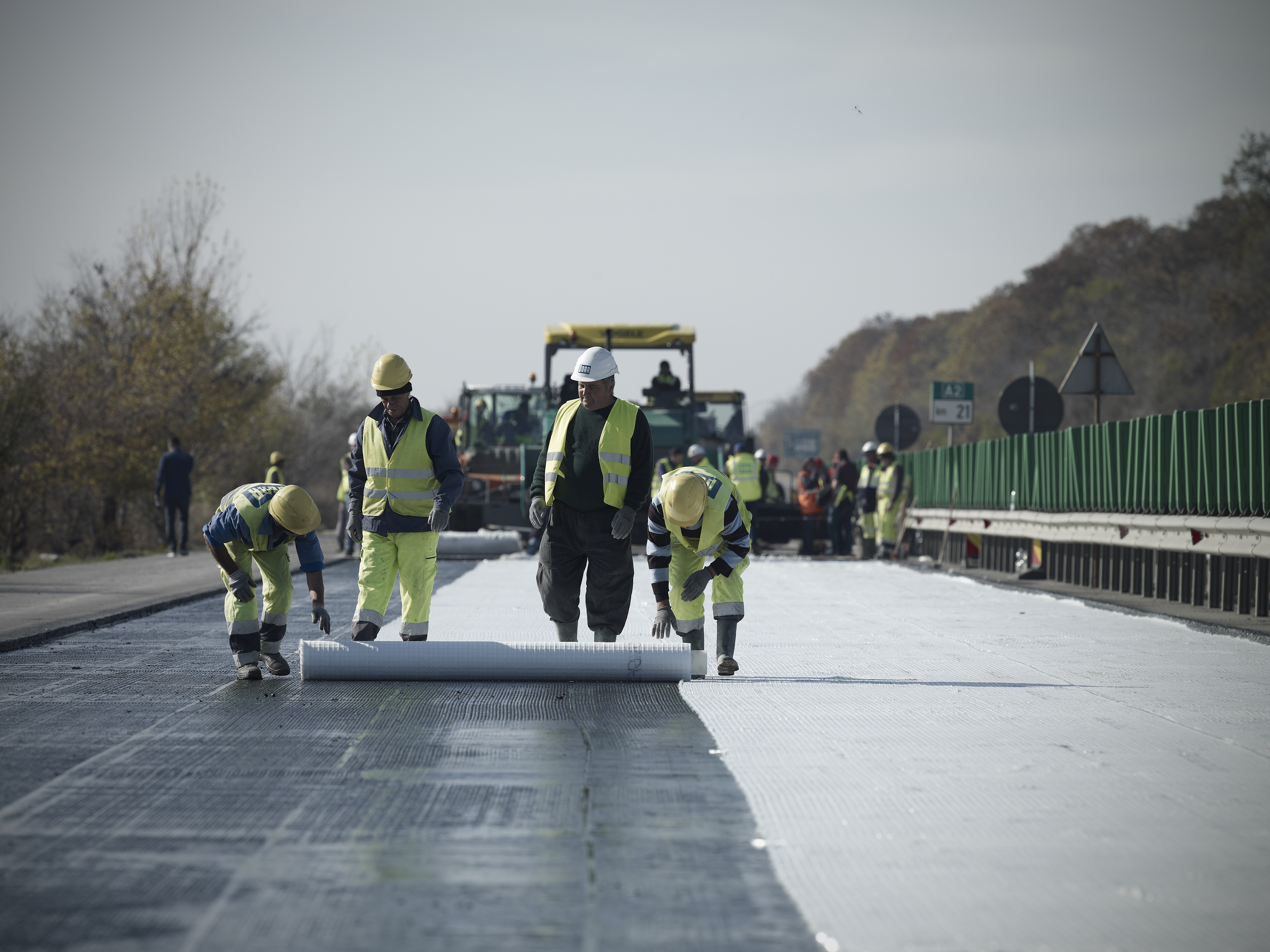 Photo: four workers rolling out a mat of fibres as interlayer on a freshly paved motorway