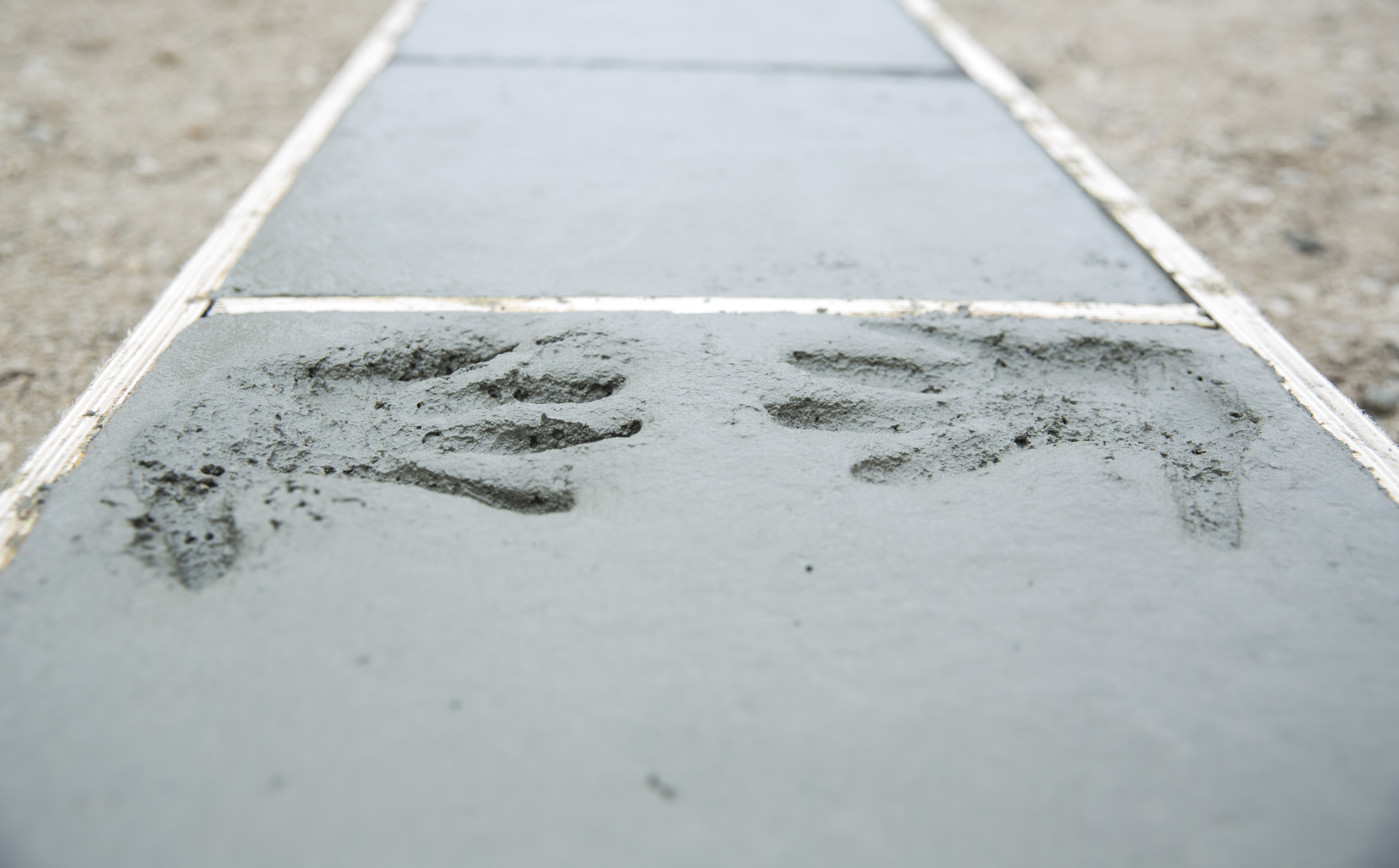Photo: two handprints in fresh cement inside a formwork